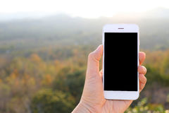 Hand holding mockup smartphone with sunlight and mountain backgr Royalty Free Stock Photos