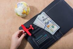 Hand holding model airplane beside globe and dollars stock photo