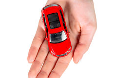 Hand holding model of a car. Isolated against a white background royalty free stock image