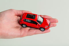 Hand holding model of a car. A hand holding a model car. photo icon for car purchase stock photo