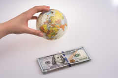 Hand holding  a model globe by the side of American dollar bankn Royalty Free Stock Photos