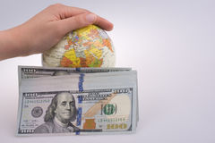 Hand holding  a model globe by the side of American dollar bankn Royalty Free Stock Images