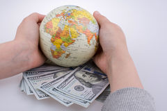 Hand holding  a model globe by the side of American dollar bankn Stock Photo