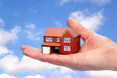 Hand holding a model home against sky background. Royalty Free Stock Image
