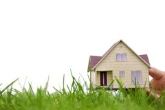 Hand holding the model of a house over green grass Royalty Free Stock Photography