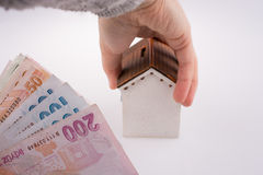 Hand holding  a model house by the side of Turkish Lira banknote Stock Photo