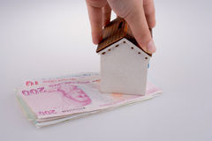 Hand holding  a model house by the side of Turkish Lira banknote Royalty Free Stock Image