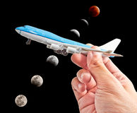 A hand holding a model phane with lunar eclipse. As background Stock Photo