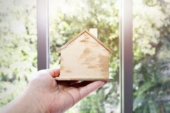 Hand holding model wood house on background.Thinking and dream royalty free stock images