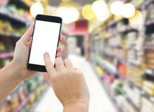 Hand holding a modern smartphone in supermarket. Someones  hands holding mobile smart phone with empty screen  on supermarket blur background business concept Royalty Free Stock Photo