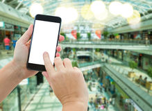 Hand holding a modern smartphone in supermarket. Someones  hands holding mobile smart phone with empty screen  on comercial center blur background business Stock Photography