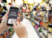 Hand holding a modern smartphone in supermarket. Someones hands holding mobile smart phone with mobile shop on supermarket blur background and shopping bags Royalty Free Stock Image
