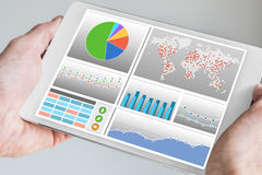 Hand holding modern tablet or mobile device with analytics dashboard