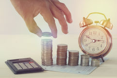 Hand holding money on pile of coins and alarm clock concept in save Stock Photography