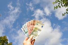 Hand holding money in the sky Stock Image
