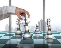 Hand holding money symbol others on table playing chess Stock Photo