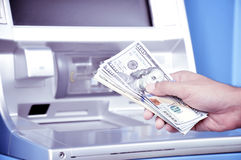 Hand holding money United States dollar (USD) banknotes in front of ATM Stock Image