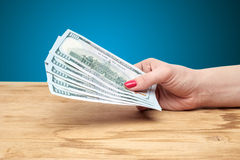 Hand holding money on a wooden table Stock Images