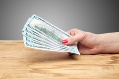 Hand holding money on a wooden table Royalty Free Stock Photo