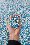 Hand holding a moutain of blue and white pills Stock Photo
