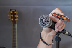 Hand holding a mouth organ and microphone. Close up of a hand holding a mouth organ and microphone during a musical performance or recital with a guitar visible Royalty Free Stock Images