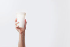 Hand holding a mug with delicious coffee in a cafe on a white ba royalty free stock images