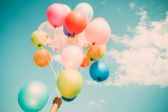 Hand holding multi colour balloons Stock Photography