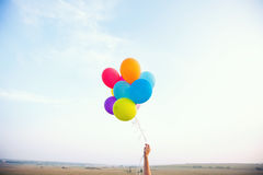 Hand holding multicolored balloons. Hand holding colorful balloons on a background of nature Royalty Free Stock Photo
