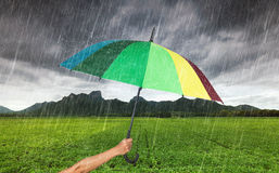 Hand holding multicolored umbrella with falling rain at Khao Jee Stock Images