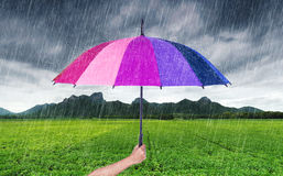 Hand holding multicolored umbrella with falling rain at Khao Jee Stock Photography