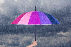 Hand holding multicolored umbrella under dark sky with rain Stock Photography