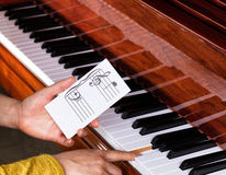Hand holding music note to play correct key on piano keyboard Royalty Free Stock Photography