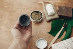 Hand holding natural eco charcoal toothpaste in glass jar on background of bamboo toothbrush, soap, solid shampoo, metal razor,. Deodorant on wood with green royalty free stock photography
