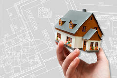 Hand holding new model house and architecture blueprint plan Royalty Free Stock Photos