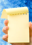 Hand holding notepad Stock Photography