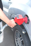 Hand holding a nozzle while fueling car Royalty Free Stock Images