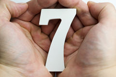 Hand holding number seven. Hand holding number seven on a white background Royalty Free Stock Images