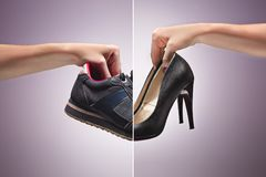 Hand Holding An Old Dirty Sneaker Shoe. Hand Holding Old Dirty Sneaker Shoes and fashionable high-heeled female shoes. Concept of confrontation, differences in Royalty Free Stock Photography