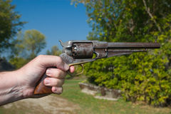 Hand Holding Old Gun. A photo of a hand holding an antique handgun in a shooting position. It is an outdoor photo on a sunny day with a blue sky and green Royalty Free Stock Photo