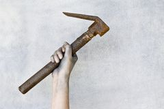 Hand holding old rusty hammer on gray background. royalty free stock image