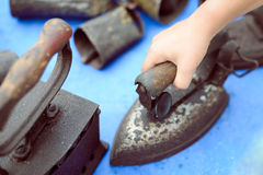 Hand holding old rusty obsolete iron standing on Royalty Free Stock Photography