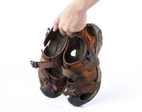 Hand holding old sandal isolated. On white background Royalty Free Stock Photos
