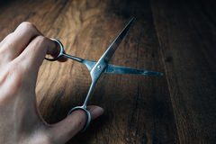 Hand holding old scissors on a wooden work table. Vintage Style Royalty Free Stock Image