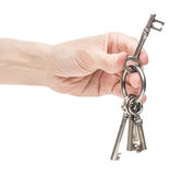 Hand holding old skeleton keys. Closeup on white background of male hand holding ring with old vintage skeleton keys royalty free stock photography