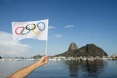 Hand Holding Olympic Flag Rio de Janeiro. RIO DE JANEIRO, BRAZIL - MARCH 24, 2015: Hand waves Olympic flag on the shore of Botafogo Bay in front of view of stock images