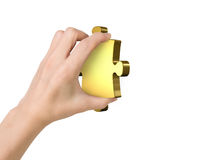 Hand holding one golden puzzle piece Stock Photos