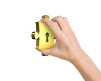 Hand holding one golden puzzle piece with keyhole. Isolated on white Royalty Free Stock Photo