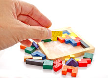 A hand holding one piece of wooden jigsaw Stock Image