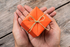 Hand Holding Orange Gift Box and Yellow Ribbon Royalty Free Stock Photo