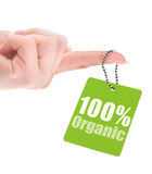 Hand holding 100% organic label. Isolated on white background stock illustration